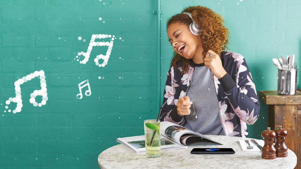 Young woman singing along to music coming from her headphones